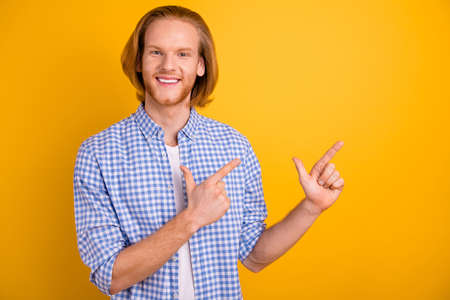 Photo of ginger foxy red headed millennial guy pointing at empty space smiling toothily beaming isolated over vibrant color background