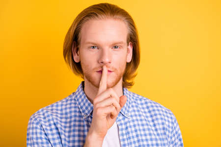 Close up photo of confident serious man showing you to stop talking saying touching his lips with forefinger isolated over vivid color background