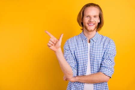 Copyspace photo of handsome student pointing at empty space away with his forefinger standing confidently isolated over bright color background Фото со стока