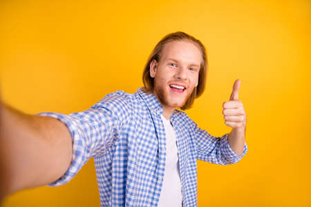 Photo of handsome cool nice cheerful guy taking selfie showing you thumb up smiling toothily beaming isolated over yellow vivid color background Фото со стока