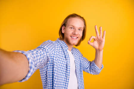 Photo of cheerful positive funky handsome checkered guy showing you ok sign taking selfie approving actions wearing blue shirt smiling toothily isolated over vibrant color background