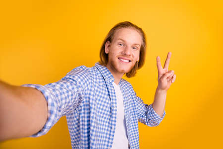Photo of cheerful handsome nice guy taking selfie showing you v-sign smiling toothily isolated over vibrant color background