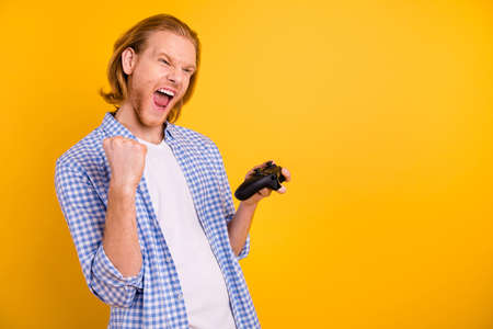 Photo of cheerful shouting rejoicing overjoyed grimacing console player celebrating his online victory holding joy stick with his hand isolated over vibrant color background Фото со стока