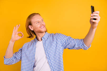 Photo of cheerful cute nice fun positive funky man blogger talking video call smiling toothily wearing checkered blue shirt taking selfie isolated over bright color yellow background