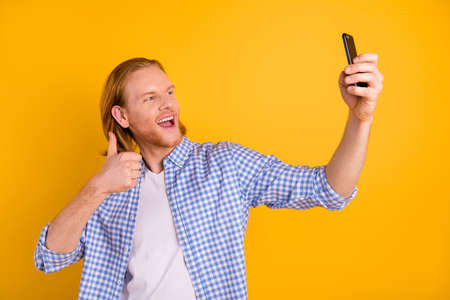 Photo of trendy stylish redhair excited man showing thumb up while blogging recording video taking selfie with phone wearing checkered blue shirt isolated vibrant color background
