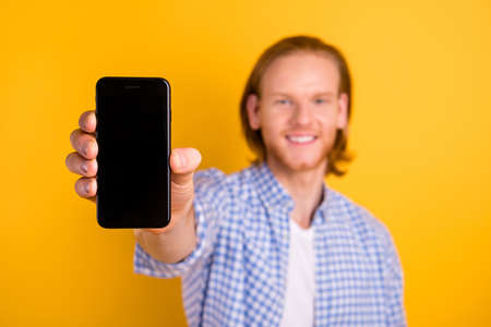 Blurred photo of trendy promoter advertising new line of smartphones with empty space on its screen hands holding isolated over vivid color background
