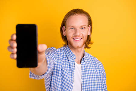 Photo of cheerful handsome promoter presenting new model of telephone smiling toothily wearing checkered blue shirt isolated over vivid color background