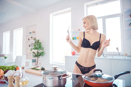 Photo of amazing slim model lady cooking breakfast for boyfriend dancing naked while preparing meal wearing underwear bra lace panties standing in light kitchen Stock Photo