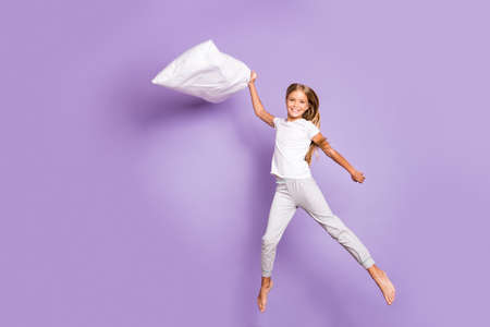 Full size photo of cheerful funny funky model preteen girl hold pillow jump have fight sleep-over party with friends enjoy weekend barefoot wear white t-shirt pants isolated violet color background Standard-Bild