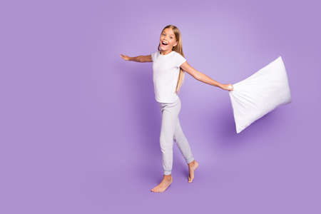 I little plane. Portrait of funky funny blonde hair cheerful kid raise hands hold pillow play game have fun on sleep-over party wear white t-shirt pants isolated violet purple color background
