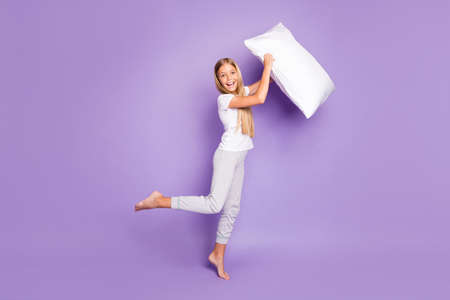 Full length photo of funny cheerful model kid hold pillow have fun on sleep-over party play game with her best friends wear white t-shirt pants isolated over purple color background