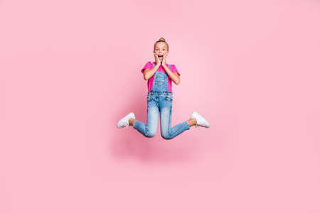 Full length body size photo of nice cute rejoicing overjoyed childish girl wearing jeans denim overall fuchsia t-shirt jumping up seeing sales isolated over pink pastel color background