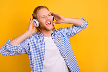 Photo of cheerful cute handsome screaming guy wearing headphones shouting words and lines of his favorite song dreaming isolated over vibrant color background