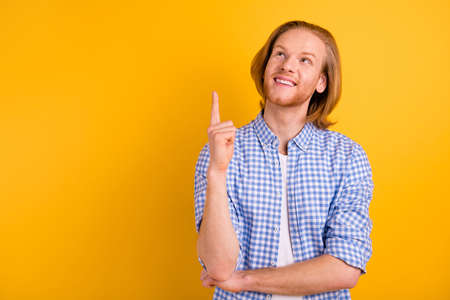 Photo of cheerful checkered beaming smiling guy pointing up at empty space wearing blue checkered shirt isolated over vibrant color background