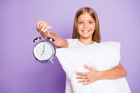 Portrait of positive relaxed blonde hair preteen model girl hold hand pillow clock show early time want hurry to school wear white t-shirt isolated over violet purple color background Stock Photo