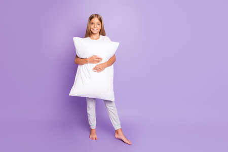 Full length photo of positive cheerful content kid hug hold carry pillow feel dreamy wakeup in morning wear white t-shirt pajama pants isolated over violet purple color background