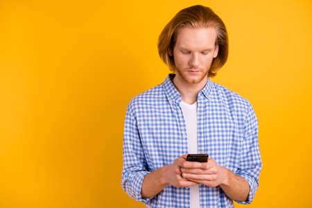 Photo of neutral concentrated focused blogger holding telephone with hands looking into phone isolated over vibrant color background