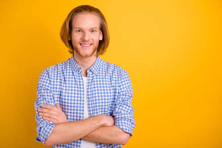 Photo of handsome attractive guy wearing blue shirt with arms crossed beaming toothy smile confident isolated over vivid color yellow background
