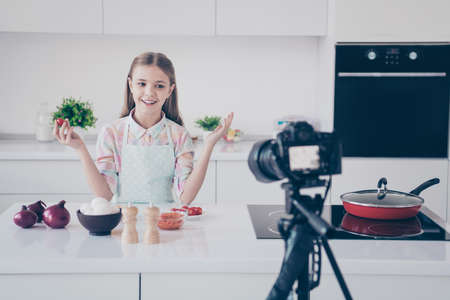 Portrait of her she nice attractive beautiful charming lovely cute cheerful cheery pre-teen girl making useful vitamin salad recording video lesson in light white interior kitchen house indoors