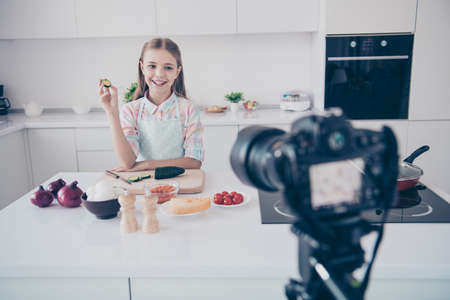 Portrait of her she nice attractive beautiful charming cute cheerful cheery pre-teen girl making useful green organic vitamin salad recording video lesson in light white interior kitchen house indoors