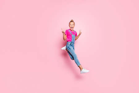 Full length body size photo of girl running fast jumping showing you double v-sign screaming with emotional facial expression wearing jeans denim t-shirt footwear isolated pastel pink color background