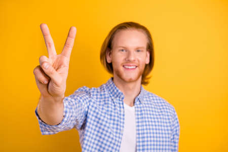 Photo of handsome cheerful guy greeting you by showing v-sign smiling toothily wearing blue shirt isolated vivid color background