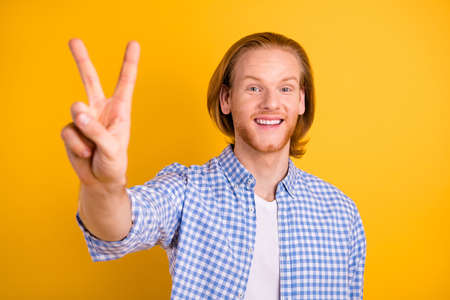 Photo of cheerful positive funny youth guy showing you v-sign saying hi wearing blue shirt isolated over vibrant color background