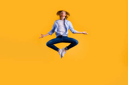 Full size photo of redhead guy jumping high meditating exercise holding body in lotus position wear casual trendy outfit isolated yellow background
