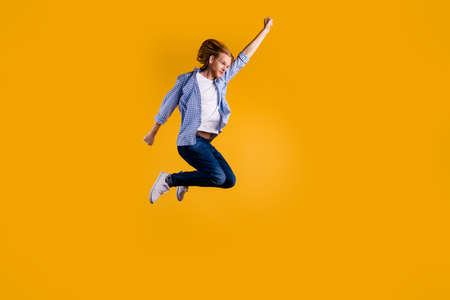 Full size photo of crazy redhead guy jumping high using super power to fly faster and save world wear casual trendy outfit isolated yellow background