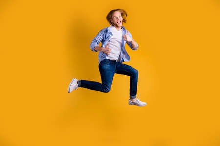 Full length body size photo of rejoicing winning carefree cheerful winner wearing jeans denim checkered blue shirt footwear showing you thumb up running jumping fast isolated over vivid yellow color background