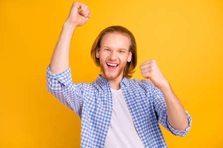 Photo of overjoyed ecstatic freelancer wearing blue checkered shirt going on vacation ready to spend summer traveling abroad isolated over yellow vivid color background Фото со стока