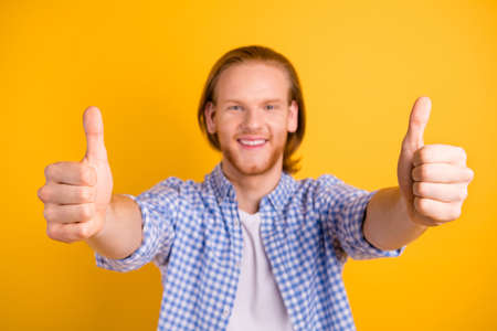 Photo of funny handsome guy gesturing you thumb up drawing your attention to his fingers up isolated over vibrant color background