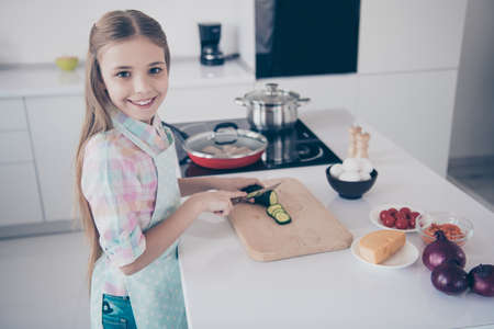 Profile side view portrait of her she nice attractive beautiful charming cute cheerful cheery pre-teen girl making useful green vegs vitamin salad in light white interior room kitchen house indoors