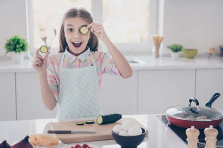 Portrait of her she nice attractive beautiful charming lovely cheerful cheery glad pre-teen girl making useful salad closing eye mask having fun in light white interior room kitchen indoors