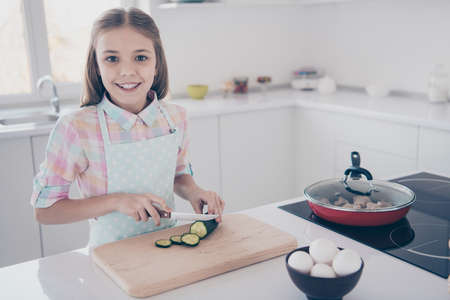 Close-up portrait of her she nice attractive beautiful charming cheery pre-teen girl making fresh useful healthy green salad preparing surprise for holiday in light white interior room kitchen indoors Stock fotó