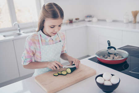 Close-up portrait of her she nice attractive beautiful charming cute pre-teen girl chopping fresh useful healthy green eco vegan vegs salad in light white interior room kitchen house indoors Stock fotó