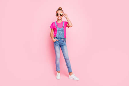 Full length body size photo of cheerful cute funny girl standing confidently in front of camera with hand in pocket wearing jeans overall footwear holding eyewear isolated over pastel pink color backg