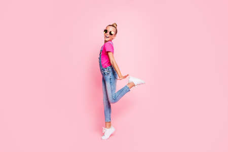 Full length body size photo of funny funky cute nice schoolgirl dancing on her holiday wearing fuchsia t-shirt jeans denim overall footwear isolated over pastel pink color background