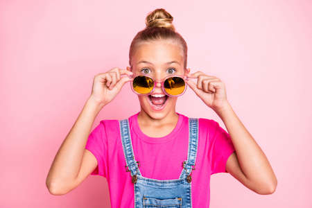 Close up photo of ecstatic cute nice funny girl looking out of her sunglass screaming rejoicing with holiday beginning isolated over pink pastel color background Banco de Imagens