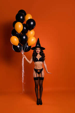 Full length vertical photo of beautiful lady toothy smiling hold many air balloons ready for private party wear bikini tights witch cap isolated orange background
