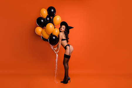 Full size photo of beautiful lady hold air balloons make private party showing husband ideal figure wear black bikini tights witch cap isolated orange background
