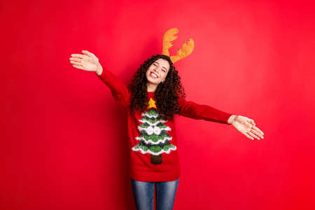 Photo of pretty curly lady with open palms meeting relatives at x-mas family gathering need much hugs wear head horns knitted pullover isolated red color background Stock Photo