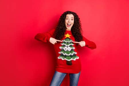 Porträt eines erstaunten lustigen, funky verrückten Mädchens, das auf ihren saisonalen Komfort-Pullover zeigt, empfiehlt ihren Pullover mit Weihnachtsbaumdekor für das Thema Weihnachts-Noel-Party einzeln auf rotem Hintergrund
