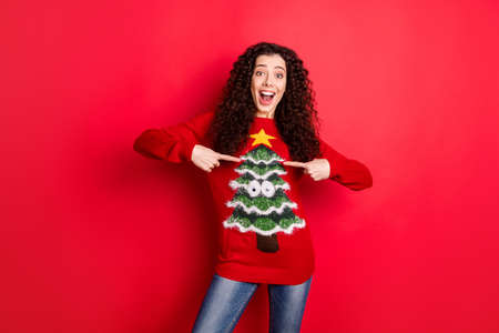 Portrait of amazed funny funky crazy girl point at her seasonal comfort jumper pullover recommend her sweater with christmas tree decor for theme x-mas noel party isolated over red color background