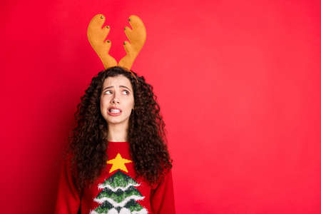 Portrait of negative funny funky girl look at reindeer headband dislike x-mas theme party costume wear seasonal trendy traditional sweater with christmas tree decor isolated red color background