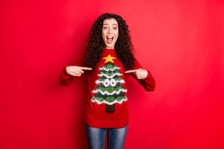 Portrait of funny funky girl point at her stylish comfort cozy season clothes sweater with christmas tree decor scream wow omg isolated over red color background