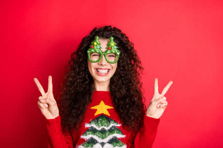 Photo of funny curly lady excited to start chilling showing v-sign symbols wear funky evergreen trees form specs knitted pullover isolated red color background Stock Photo