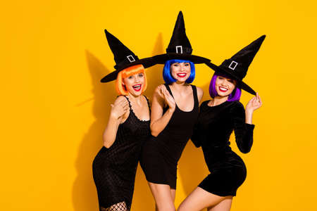 We are not zombies we are pretty kind ladies. Photo of attractive nice glad positive sweet girls believe in superstitions black cats ghost potion wand isolated vivid color background