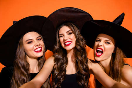 Photo of three cruel witch ladies making selfies showing evil facial expression reveal teeth wear black wizard hats isolated orange color background 写真素材 - 130723915
