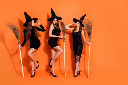 Full length photo of three wizard ladies holding brooms waiting beginning of night flight wear black dresses and hats isolated orange color background